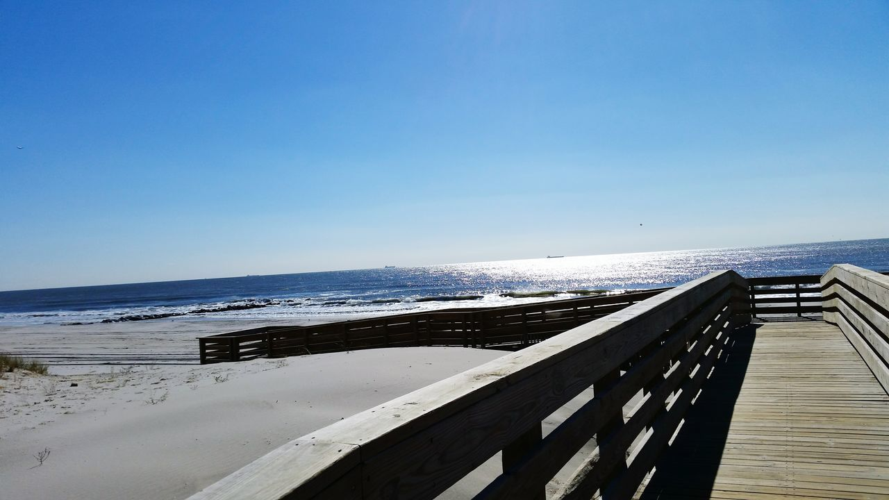 sea, horizon over water, water, beach, tranquility, tranquil scene, scenics, nature, day, beauty in nature, no people, blue, wood - material, outdoors, clear sky, sunlight, sky, sand