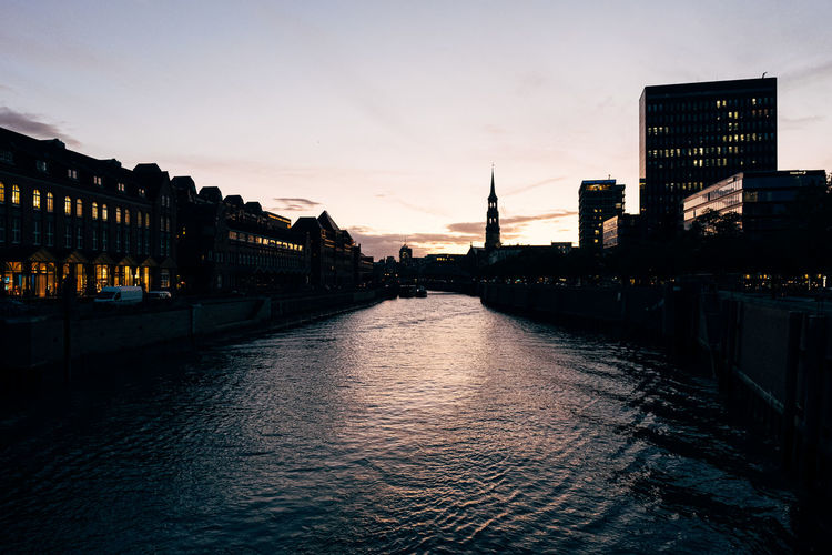 River amidst illuminated buildings against sky at sunset