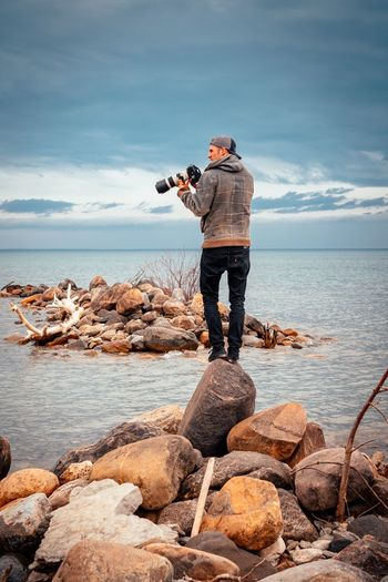 Full length of man photographing on rock at beach against sky
