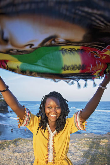 Portrait Of Woman Holding Scarf While Standing At Beach