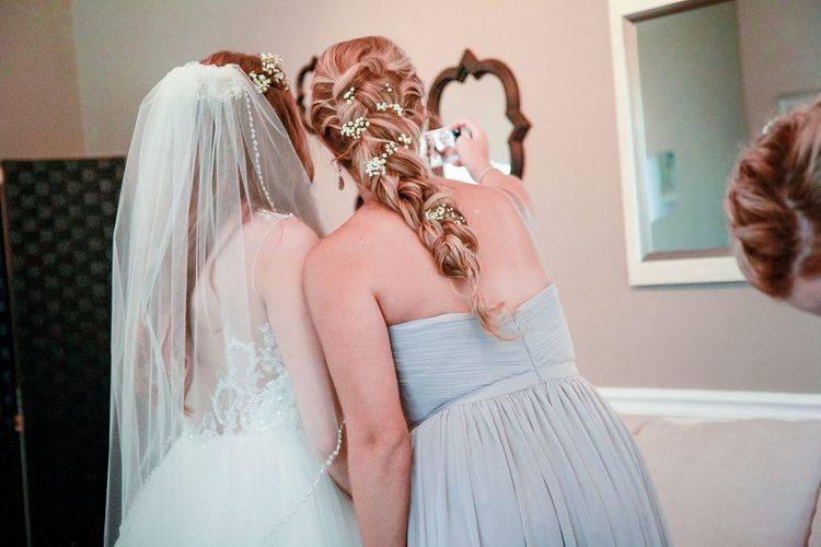 Bride with bridesmaid taking selfie in wedding ceremony