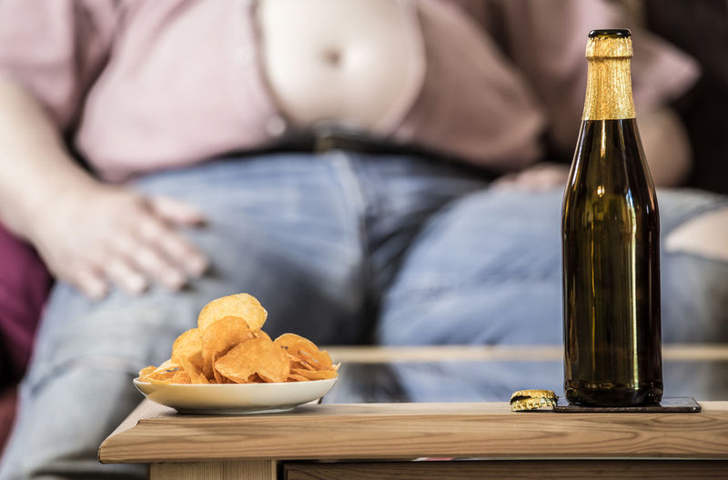 Midsection of senior man with beer and potato chips on table sitting at home