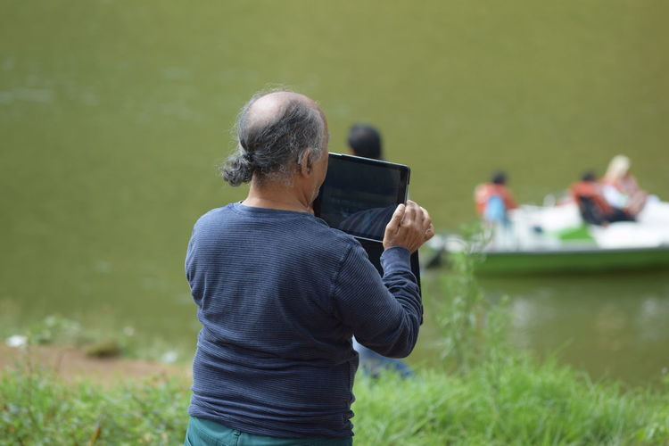Rear View Of Man Photographing Through Digital Tablet By Lake