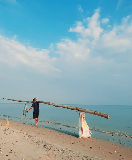 Boy on beach by sea against sky