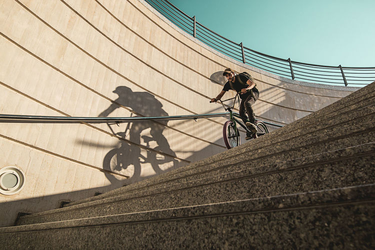 Low angle view of man riding bicycle on staircase