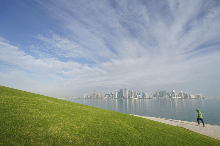 Wide View Man Walking in Water Front Cityscape of Doha, Qatar. Grass Sky Plant Beauty In Nature Nature Cloud - Sky Green Color Day Rear View Scenics - Nature Lifestyles Land Field Tranquility Architecture Women People Men Outdoors Ijas Muhammed Photography Doha Qatar Morning Cityscape Park