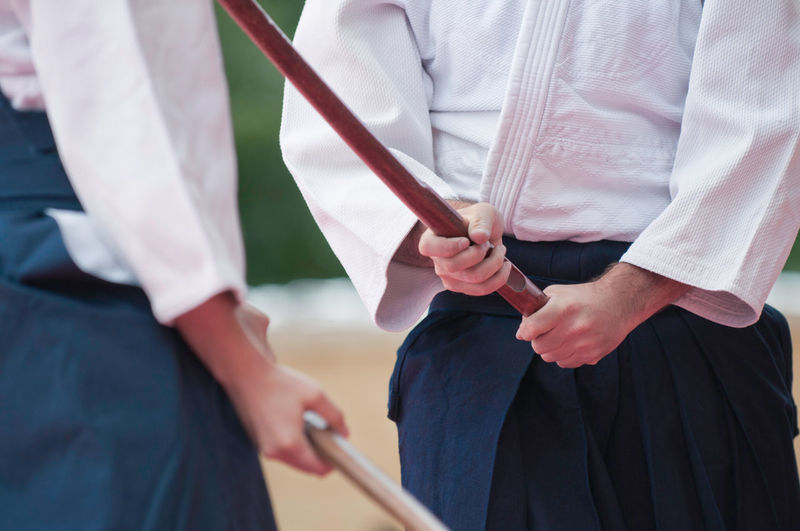 Midsection Of Men Holding Sticks
