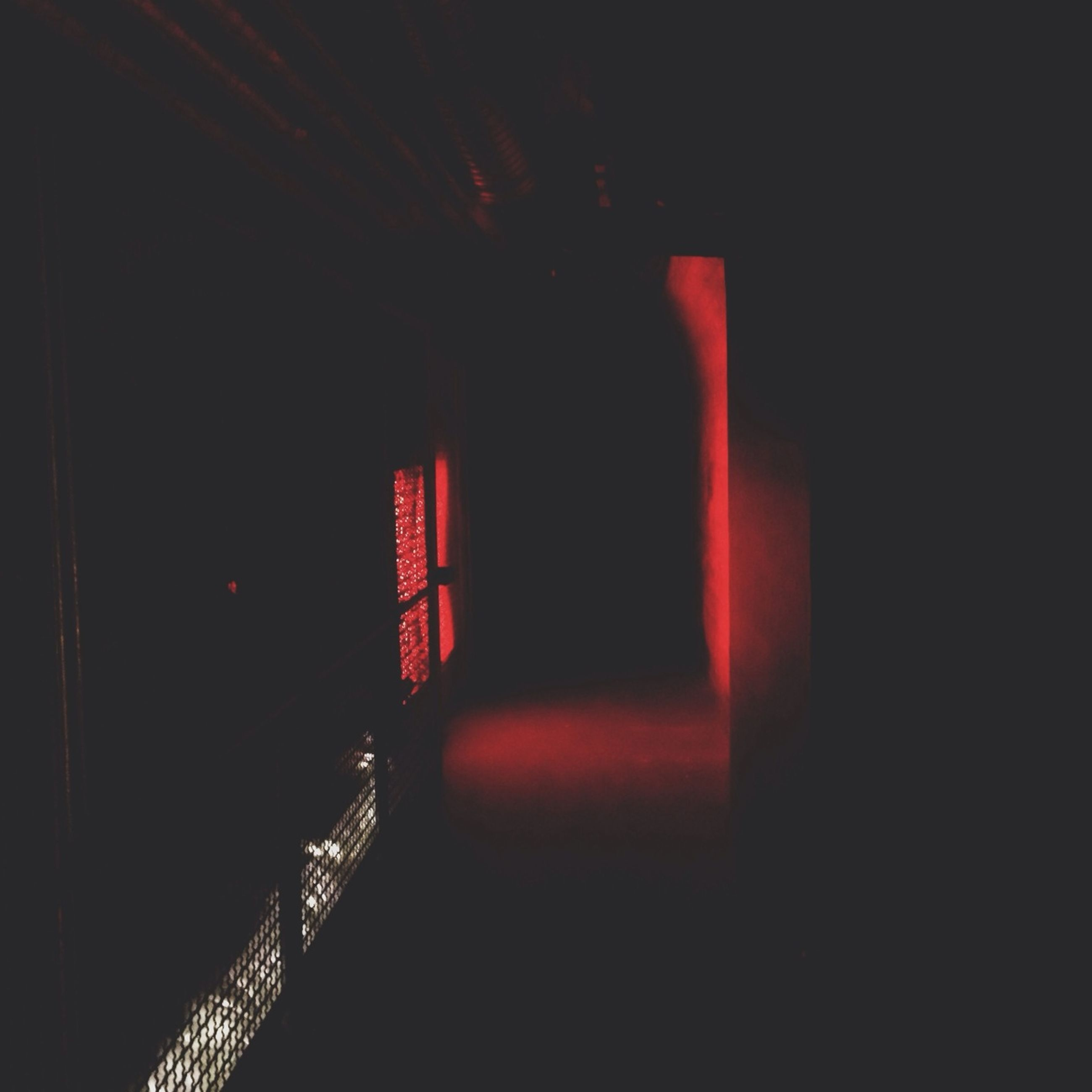 illuminated, indoors, architecture, built structure, night, red, dark, lighting equipment, copy space, light - natural phenomenon, no people, wall - building feature, low angle view, building, building exterior, glowing, light, railing, electric light, wall