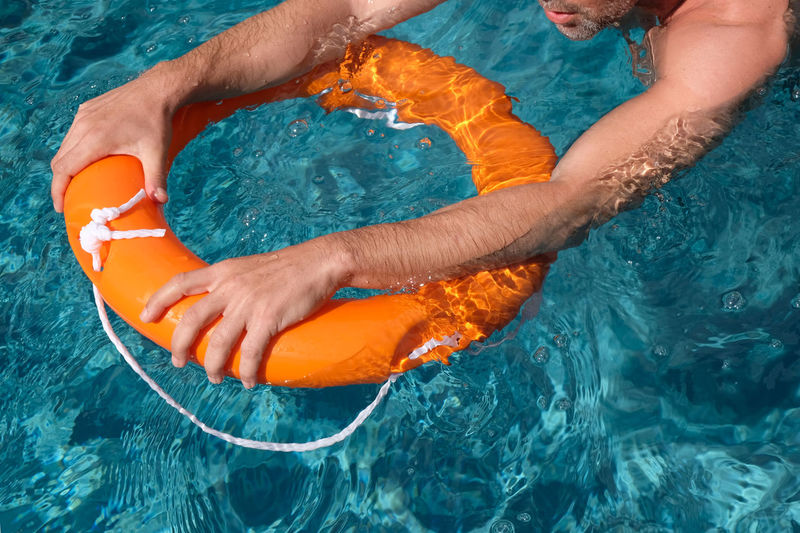 Cropped hands of man holding life belt in pool