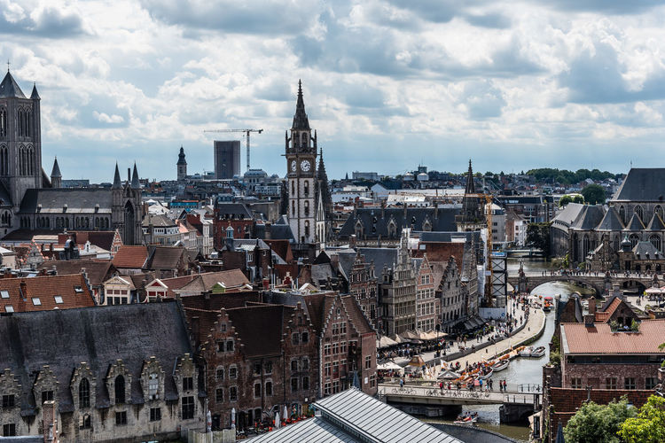 Belfry of ghent by buildings against cloudy sky
