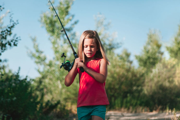 Girl holding fishing rod while walking in forest