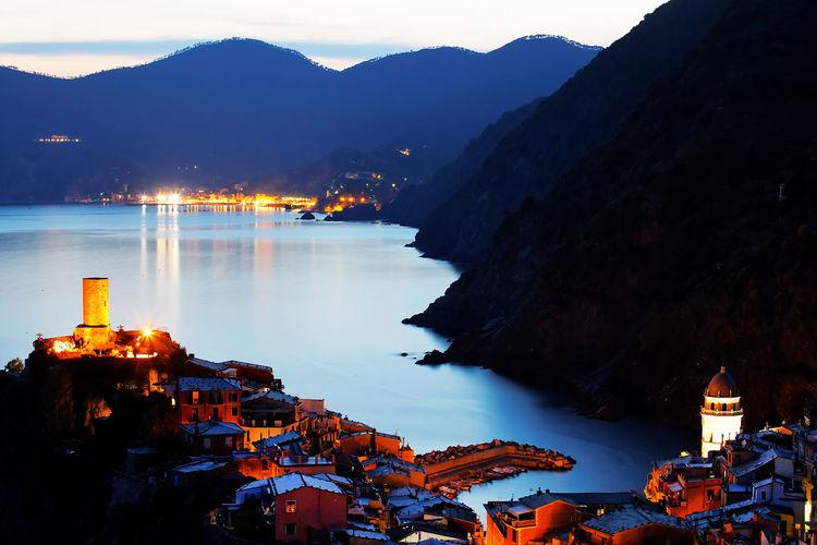 Illuminated village at mountain by sea during sunset