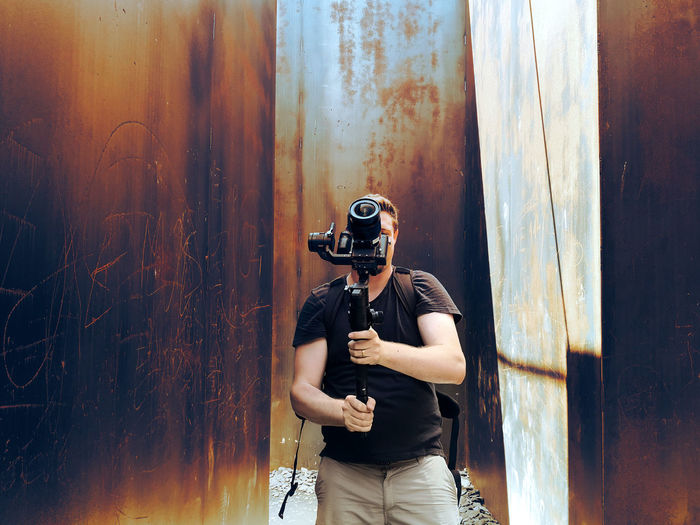 Man holding camera standing against rusty metal wall