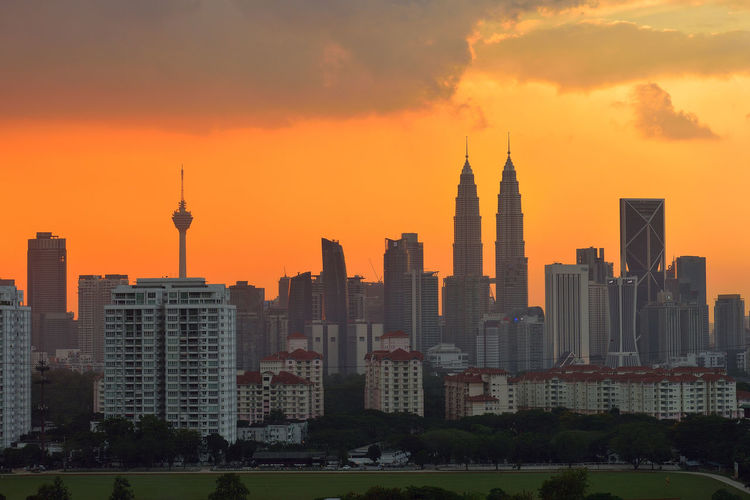 Menara kuala lumpur and petronas towers against sky during sunset in city