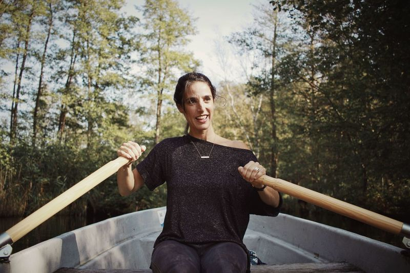 One Person Leisure Activity Lifestyles Smiling Healthy Lifestyle Sitting Tree Outdoors Day Real People Exercising People Sport Only Women Happiness Adults Only Young Adult Adult One Woman Only Young Women Bridge Rowing Rowboat Beautiful
