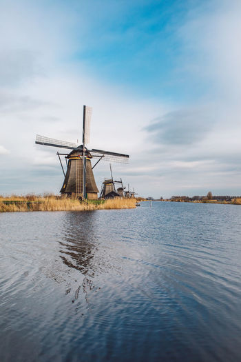 Traditional windmill on shore against sky