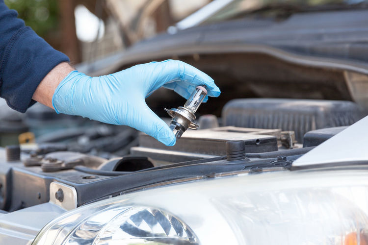 Changing halogen bulb in car headlight. Car service, installation of new car headlight bulb Hand Car Motor Vehicle Mode Of Transportation Transportation Light Bulb Headlight Halogen Car Service Holding Gloves Replacing Replace Replacement Car Parts Electricity  Visibility Automobile Maintainance