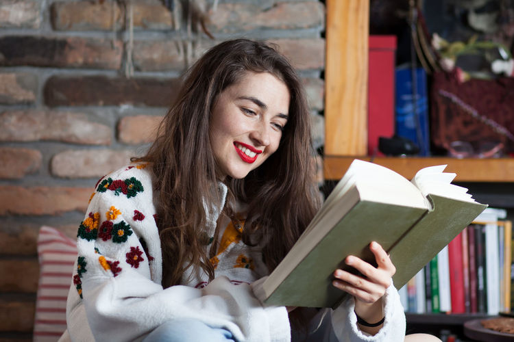 young woman reading a book Absorbing Captivated Learning Sitting Student Beautiful Woman Book Brick Wall Brunette Education Holding Immersed Knowledge Leisure Activity Lifestyles Long Hair Novel One Person Portrait Publication Reading Smiling Studying Women Young Adult