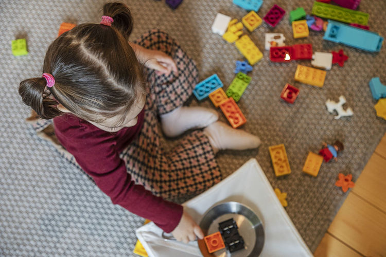 High angle view of girl playing with toy at home