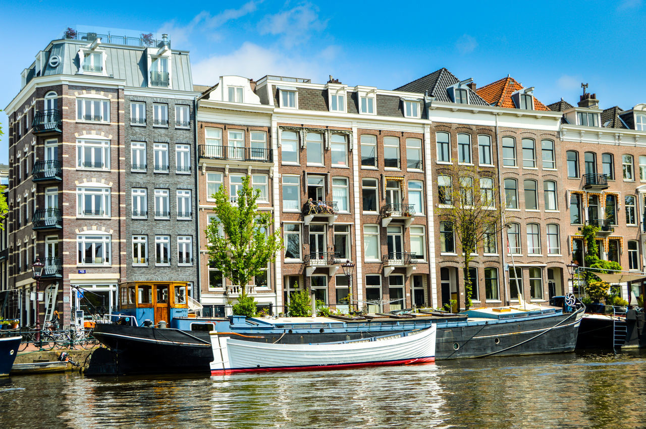 architecture, building exterior, nautical vessel, built structure, canal, water, mode of transport, waterfront, moored, transportation, travel destinations, window, outdoors, day, residential building, sky, city, no people, gondola - traditional boat