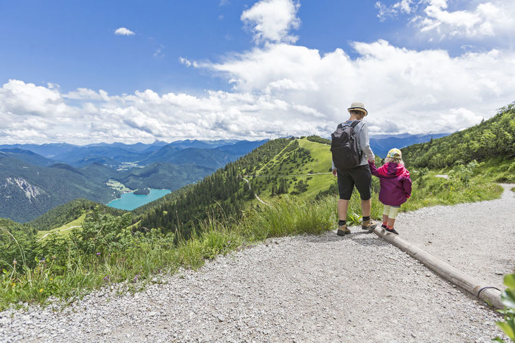 Mother And Daughter Hiking On Mountain Road Against Sky