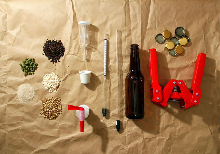 Ingredients By Beer Bottle And Equipment With Bottle Capper On Paper