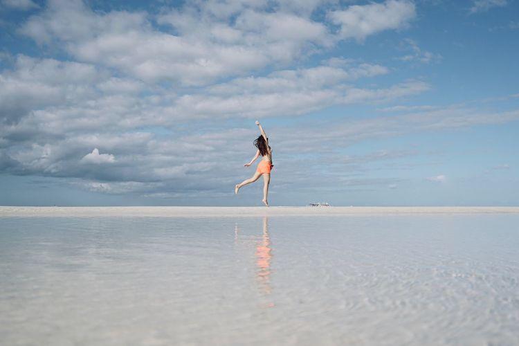 Woman dancing at beach against sky