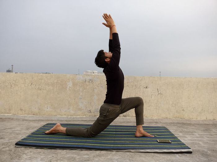 Full length of man with arms raised exercising against sky