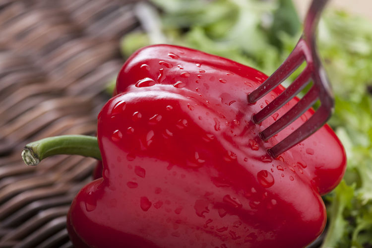 Close-Up Of Fork On Wet Red Bell Pepper