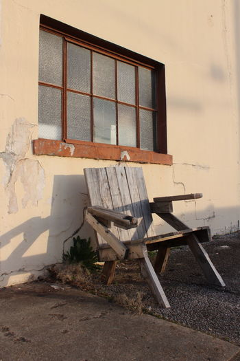 Old wooden chair against house