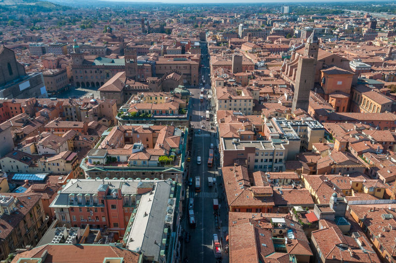 Aerial view of red tiled rooftops and street with traffic in bologna, italy.