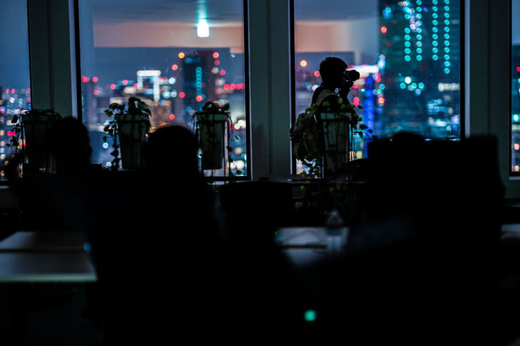 Silhouette people standing in illuminated building at night
