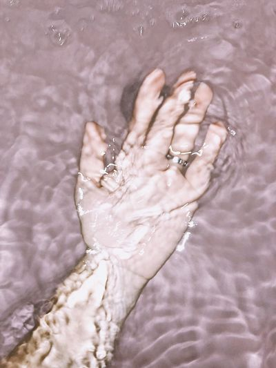 High angle view of person hand in water