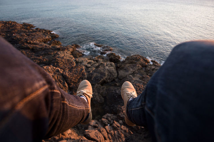 Low section of men sitting on rock by sea
