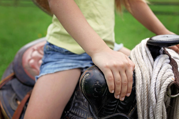 Midsection of woman holding rope sitting outdoors
