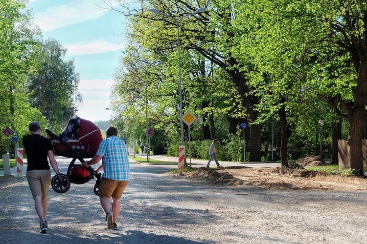 Rear view of people walking on road against treesidental