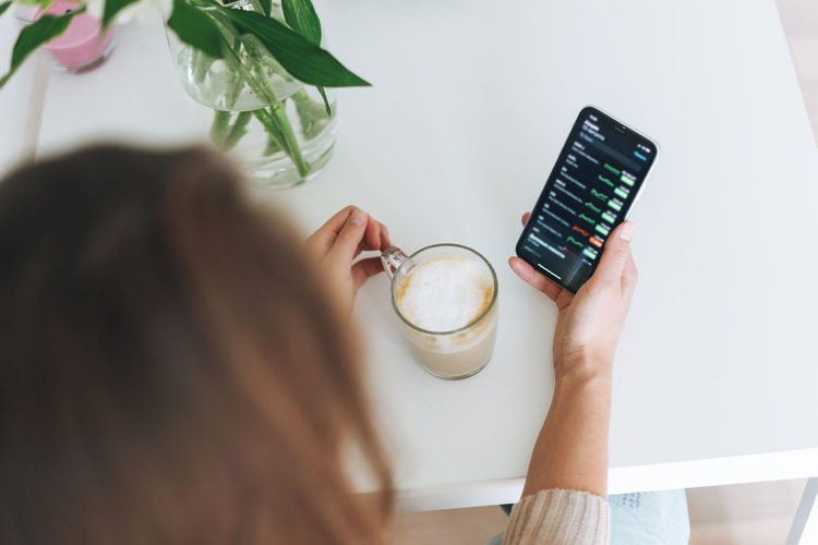 Young woman checking cryptocurrency charts and stock quotes on mobile phone with cup of coffee