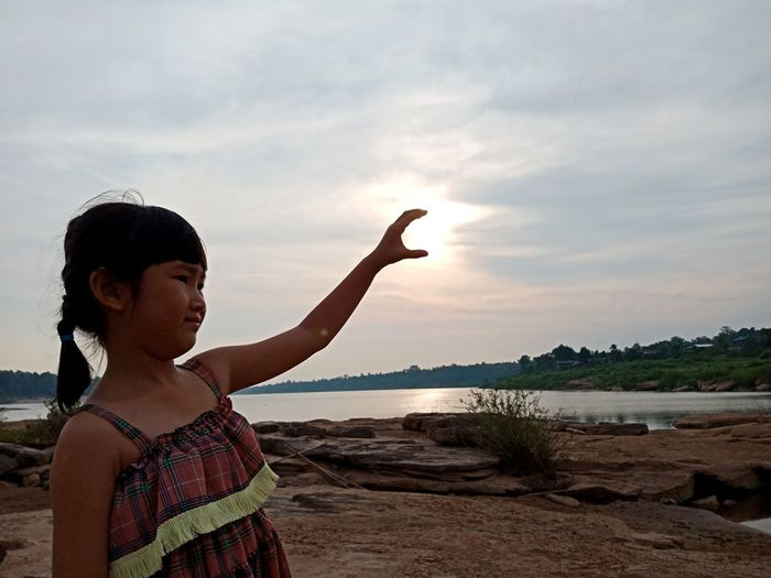Girl standing by lake during sunset