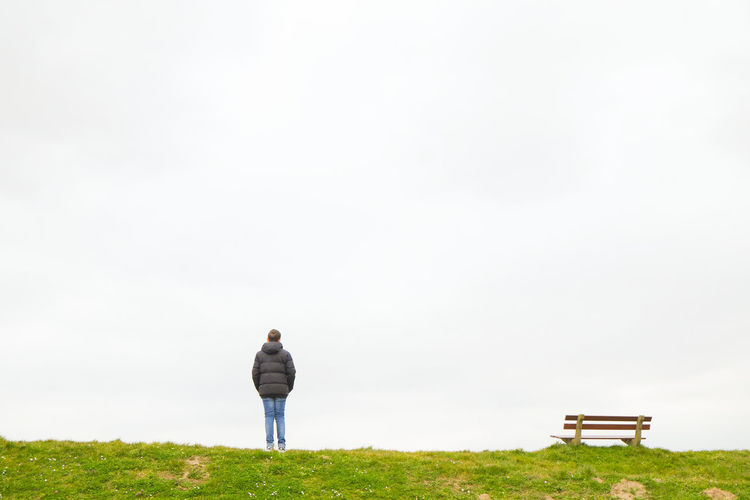 A single person standing next to a single empty wooden bench on the horizon above a grass field against a large grey clouded sky depicting loneliness, thinking, pondering, grieve, being alone, sadness One Person Grass Rear View Full Length Standing Copy Space Land Plant Sky Day Nature Field Casual Clothing Leisure Activity Environment Adult Men Outdoors Beauty In Nature Contemplation Looking At View
