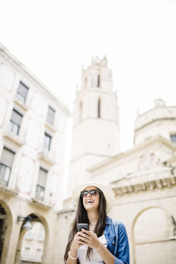 Low angle view of cheerful young woman using smart phone against building