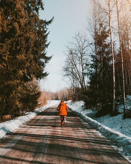 Rear view of woman running on road during winter
