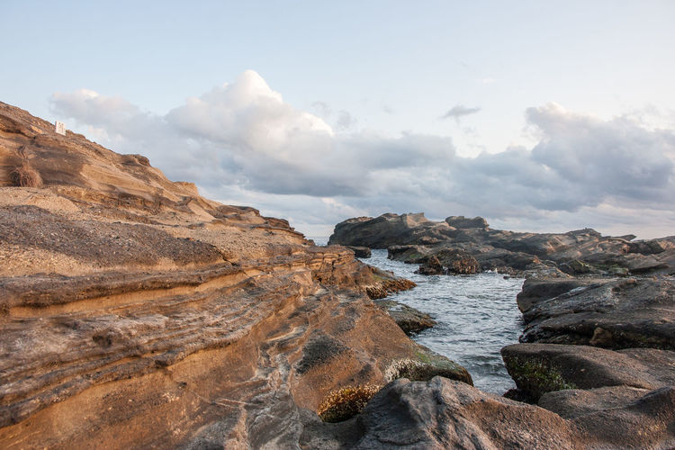 Scenic view of rock formations at sea shore against sky