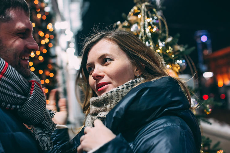 Portrait of woman with illuminated christmas tree during winter