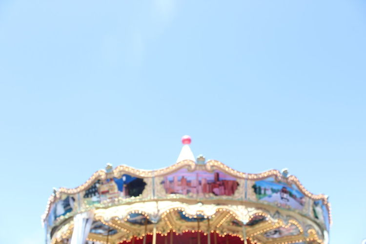 Low angle view of amusement park against clear blue sky