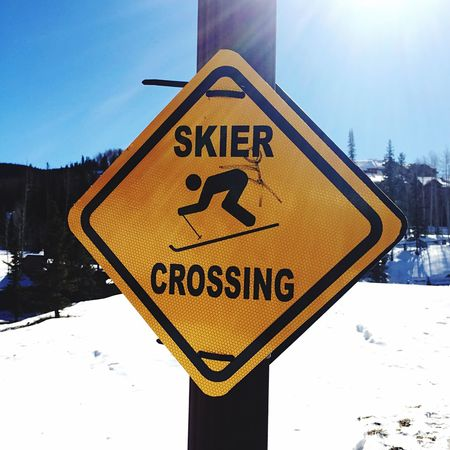 Yellow Skiers crossing Sign in Mountain village Ski Slope in the background