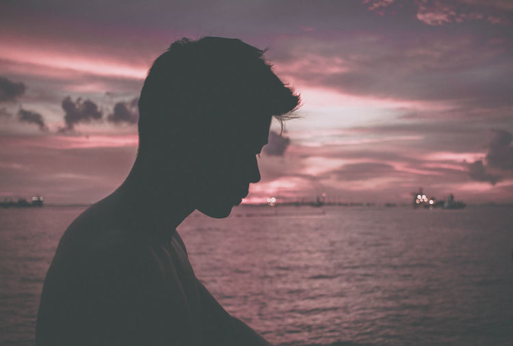 Portrait of silhouette man in sea against sky during sunset