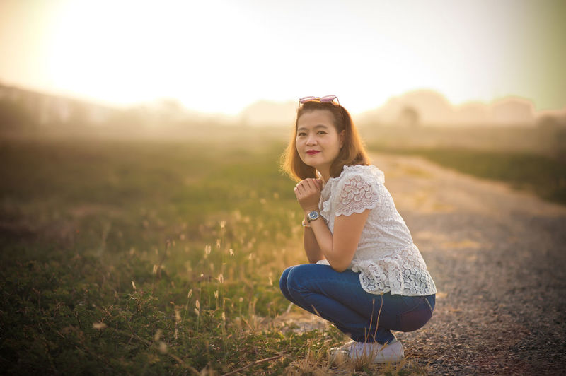Portrait of woman crouching on field against sky during sunset