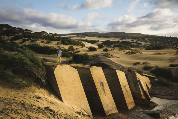 Scenic view of old dam with hiker and sand dunes of piscinas sardinia