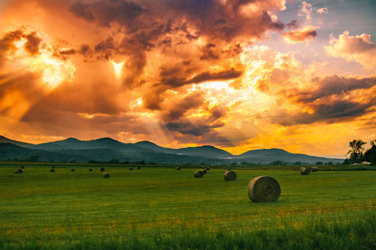 Hay bales on field against sky during sunset