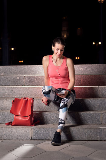 After the workout: a beautiful young woman in sport clothes (tank top leggings and running shoes) relaxes and listens to music sitting on stone steps after her evening run in the city One Person Front View Real People Full Length Lifestyles Young Adult Sports Clothing Leisure Activity Steps And Staircases Adult Sitting Clothing Night Bag Outdoors Beautiful Woman Workout Copy Space Black Background Active Lifestyle  Healthy Lifestyle Music Phone Smartphone Earbuds City Urban Evening Purple Leggings No Logos Running Shorts Relaxing Pretty Casual Clothing Sport Clothes Pink Color Tank Top Street Happy Caucasian Exercise Female Style Stone Space For Text Space For Copy